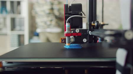 impressão digital : Close-up of 3D printer working making plastic thing while person African American man is walking in background. Machines and modern technology concept.