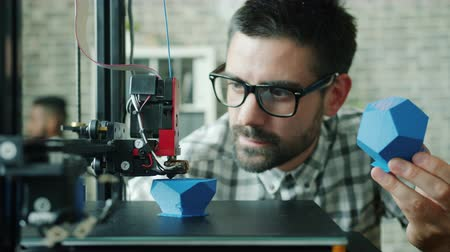 impressão digital : Young man in glasses is looking at 3D printer printing plastic model in office holding the same shape. Modern technology, people and innovation concept.