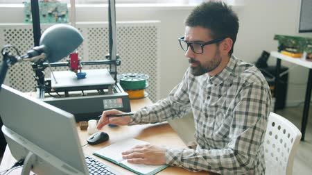 impressão digital : Handsome guy in glasses is working with computer while modern 3d printer is modeling plastic shape in background. People, work and innovation concept.