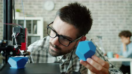 impressão digital : Male researcher watching 3d printer making plastic detail enjoying process holding polymer model in hand comparing shapes. People, technology and design concept.