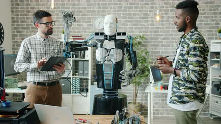 inventing : Joyful young men are testing robot with tablet working together in modern office, electronic machine is moving arms. Innovative business and technology concept. Stock Footage