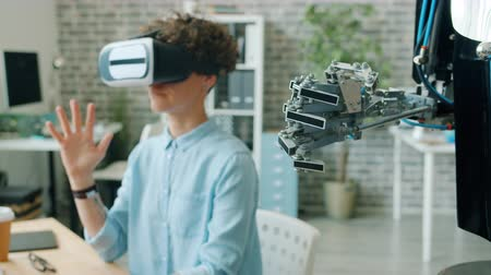 inventing : Robotic hand is moving like human while girl in vr glasses scientist is testing new robot in office. Modern technology, devices and robotics concept. Stock Footage