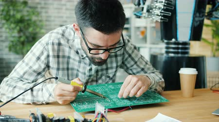 soldering iron : Young male worker is fixing robot motherboard with soldering iron in office, human-like droid is visible in background. People, engineering and profession concept. Stock Footage
