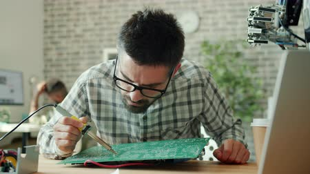 microélectronique : Slow motion of handsome man fixing motherboard with soldering iron in office, human-like robot is visible in background. People, work and robotics concept. Vidéos Libres De Droits