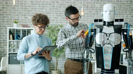 inventing : Girl and guy robotic engineers are testing robot functions using modern equipment tablet in office discussing artificial intelligence. Work and engineering concept.