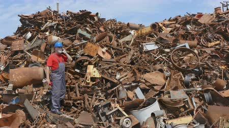 destruct : Metal recycling, worker speaking by mobile phone at heap of scrap metal Stock Footage