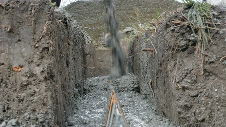 earthworks : Pouring concrete to trench at construction site with shovel and reinforcement