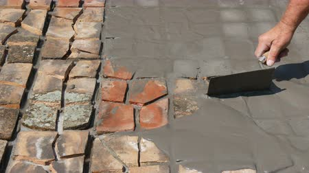 cserepezés : Worker spreading mortar to recycled tiles floor using trowel tool Stock mozgókép