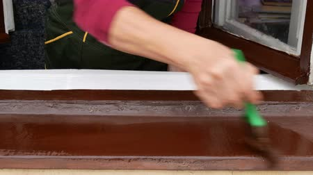 ручная работа : Worker paint old metal exterior window sill to brown color, closeup of hand with brush tool