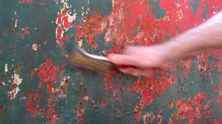 Rust removing from metal using wire brush, closeup of hand with tool