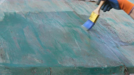 Worker applying rust converter to old metal plate, closeup of hand and brush tool
