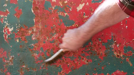 Rust removing from old metal roof plate using wire brush, closeup of hand with tool
