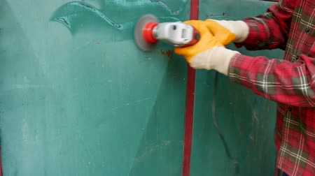 Paint and rust removing from old metal door using wire brush at grinder power tool Stock Footage