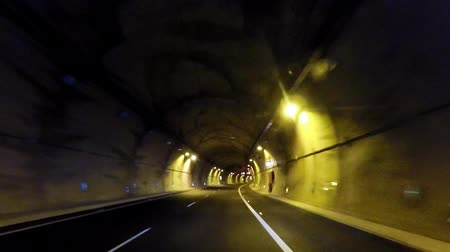 oppression : driving in a tunnel under the mountain with lights and road signs