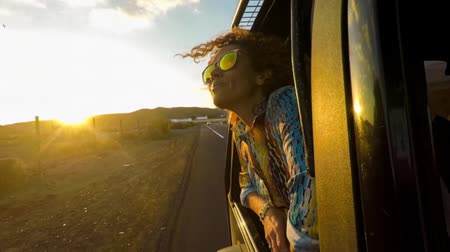 positive vibes : woman head outside the window with sunset on face Stock Footage