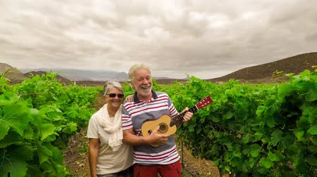 zęby : elderly man and woman playing with an ukulele in vineyard