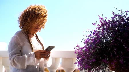positive vibes : young woman using a phone in her terrace field Stock Footage