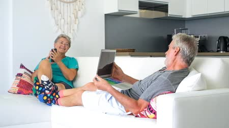 positive vibes : elderly couple enjoying technology using mobile phone and laptop indoors Stock Footage