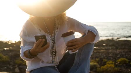 hale : Portrait of beautiful lady using the phone, holding a coffee, under a big hat Stok Video