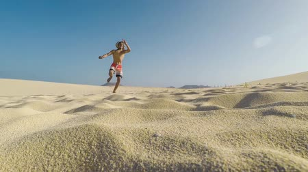 szőke : young and attractive boy having fun and enjoy walking and jumping on sand. holiday summer vacation concept for people who love