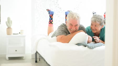 iluminado para trás : Elderly couple playing in the bed