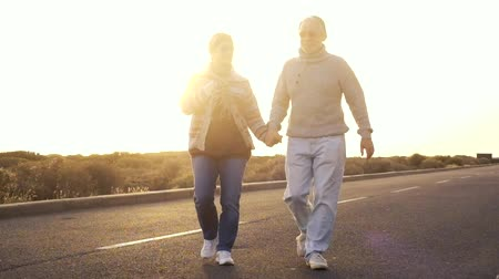 hippie : Elderly caucasian couple walking on the sunset