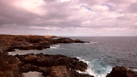 kanarya adaları : Seascape with cliffs and lighthouse in Tenerife Stok Video