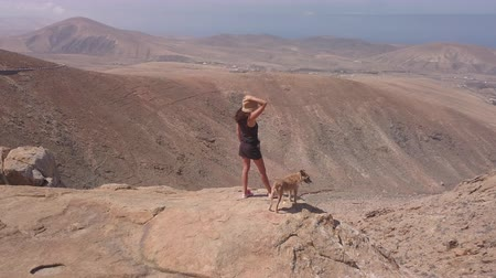 fuerteventura : young girl with her dog puppy looks at the view on the summit of a
