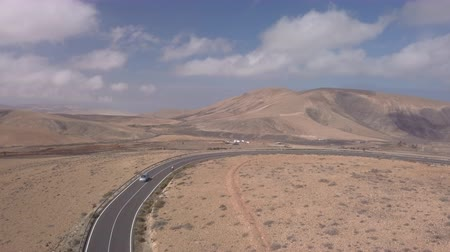 canário : 2018-10-03 Fuerteventura: cyclist runs along a hilly road in an arid landscape Stock Footage