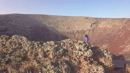 fuerteventura : young girl arrives on the top of the volcano Stock Footage