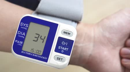 Man checks blood pressure. Wrist meter close up.