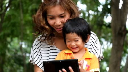 таблетка : An Asian boy and mother are playing funny game on tablet.
