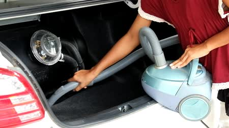 cleaner : Woman vacuuming car trunk, clean dirty car trunk with handy vacuum