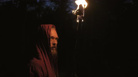 казна : Man in monastic robe with burning torch