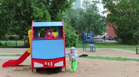 outdoor : Little happy girl sits in wooden car and baby boy stands near it at playground