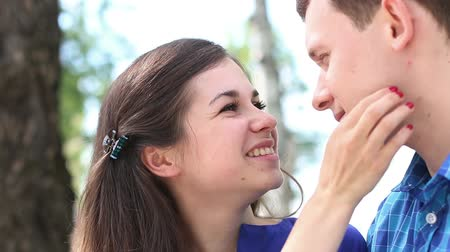 bochecha : Happy woman looks at young man and kisses him outdoor Stock Footage