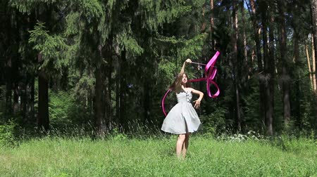 stuha : Young woman in dress dances with pink ribbon in summer forest Dostupné videozáznamy