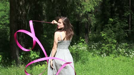 fitas : Pretty girl in dress goes back to forest and twists pink ribbon