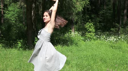 giydirmek : Beautiful happy girl in grey dress dances in summer forest