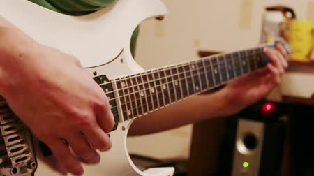 person's hand : Hands of young man playing modern white guitar at home
