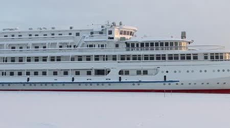 hibernation : Big tourist liner on frozen river at winter snowy day