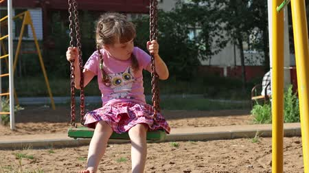 little : Little girl in pink swings at playground at sunny day