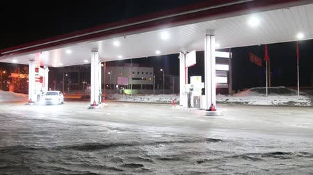 benzin : Car comes to petrol station and refuel at night in winter. Time lapse Stok Video