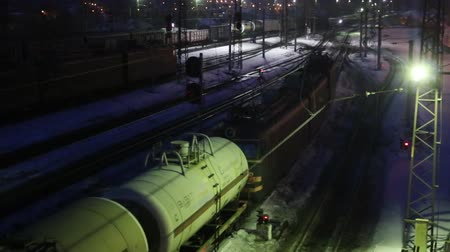 modern train wagon : Long freight train moves on railway at winter night Stock Footage