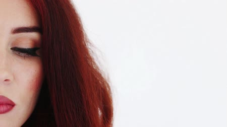 operacja plastyczna : Half of face of blinking woman with red hair. Close up Wideo