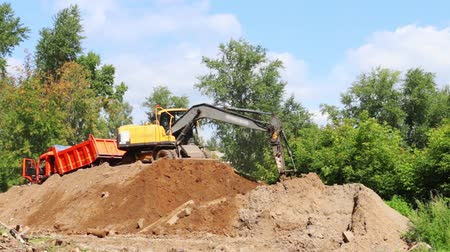 trucks : Excavator on hill loading sand into truck in summer