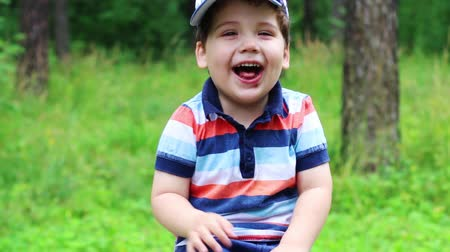 outside view : Little cute boy in cap laughs in summer park. Close up view