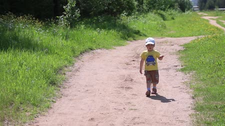 stomping : Little boy walks on forest path in middle of green grass in summer sunny day