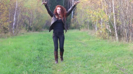 couro : Pretty young woman in leather jacket poses and dances in autumn forest