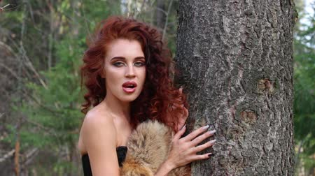 kudrnatý : Pretty young woman poses as animal near tree in autumn forest at sunny day